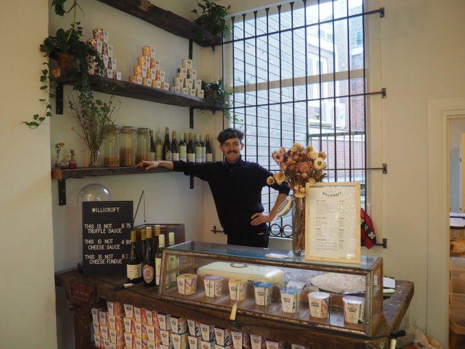 Der Gründer von Willicroft steht hinter einer Ladentheke. Dort wird veganer Käse verkauft