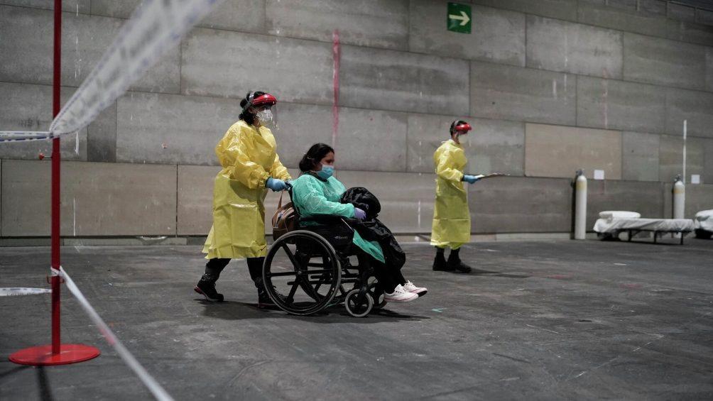 Eine Krankenschwester schiebe eine Corona-Patientin in einem Rollstuhl durch eine Halle